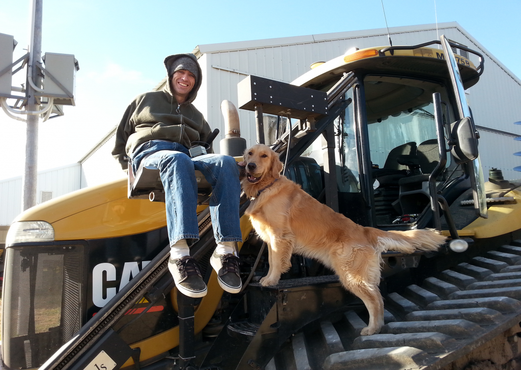Man on lift going up to tractor seat with dog.